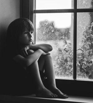 Niño triste sentado en una ventana para representar a los niños con baja autoestima