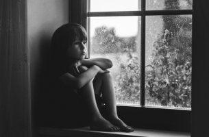 Niño triste sentado en una ventana