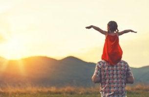 Padre con hija en hombros mirando al sol