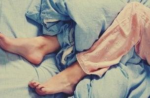 mujer en la cama que sufre síndrome de las piernas inquietas