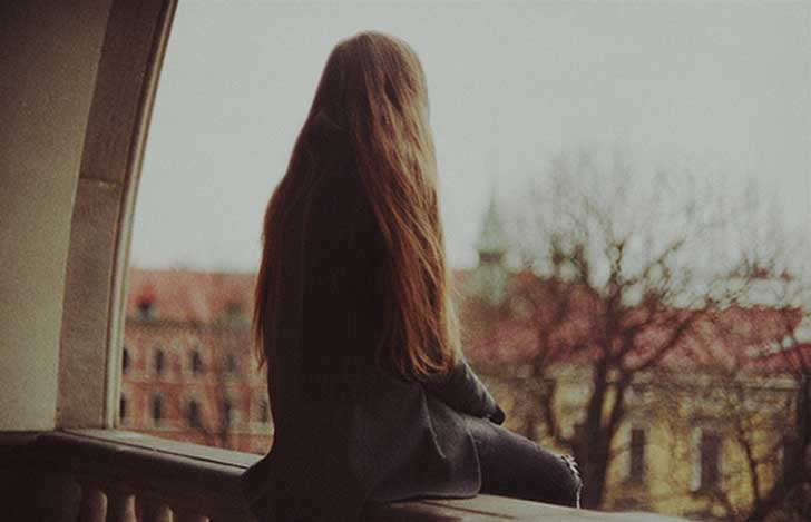 Chica en una ventana pensando en la soledad
