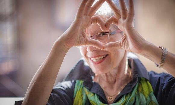 mujer mayor feliz haciendo corazón con las manos satisfecha por envejecer saludablemente