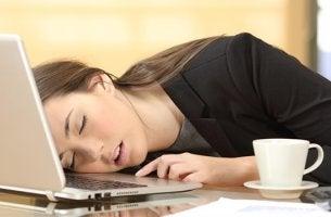 Chica dormida sobre el ordenador con narcolepsia