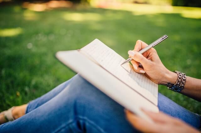 mujer escribiendo sobre sus ejercicios de yoga en casa