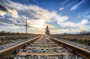 Chica de pulseras andando por la vía del tren