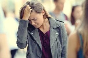 Mujer con la mano en la cabeza por el malestar originado por la fuga disociativa