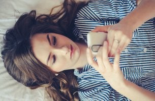 Chica tumbada con el móvil