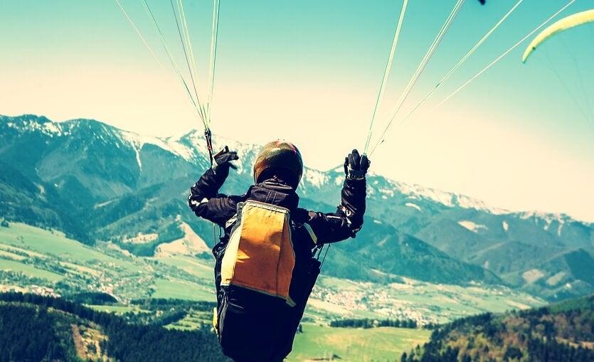 chico con paracaídas representando la atracción por las conductas de riesgo