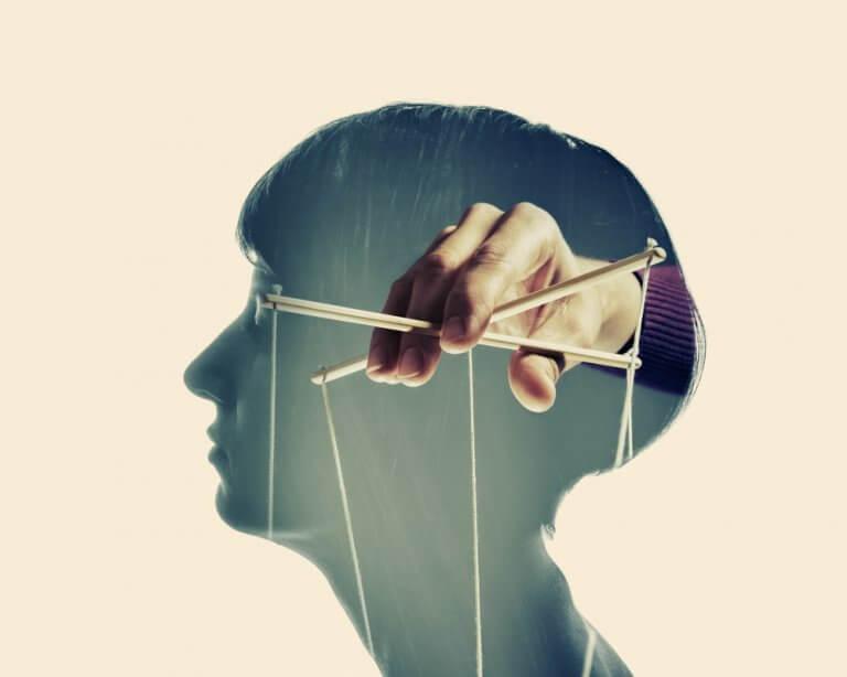 Mano manejando los hilos de una marioneta en la mente de una persona