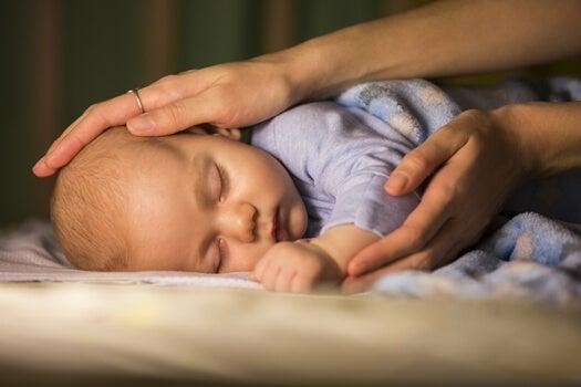mano acariciando bebé representando la comunicación kinestésica
