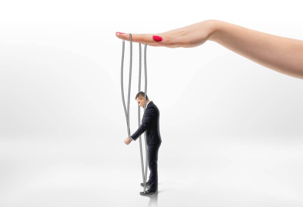 Mano sujetando la marioneta de un hombre