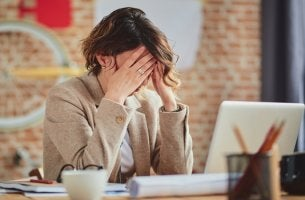 mujer en el trabajo con dolor de cabeza que piensa en tomar Sumial (Propranolol)