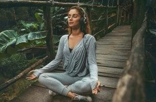 mujer en posición de loto escuchando música relajante