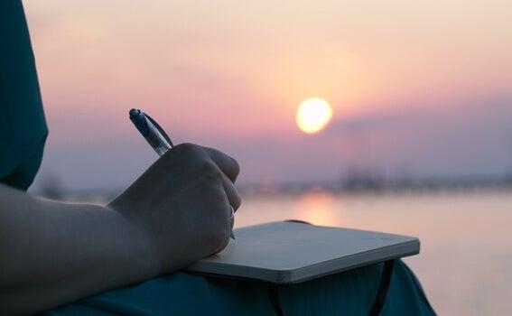 mujer escribiendo al amanecer simbolizando el arte de expresar el dolor emocional
