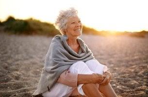 mujer mayor sentada en la playa feliz por envejecer saludablemente