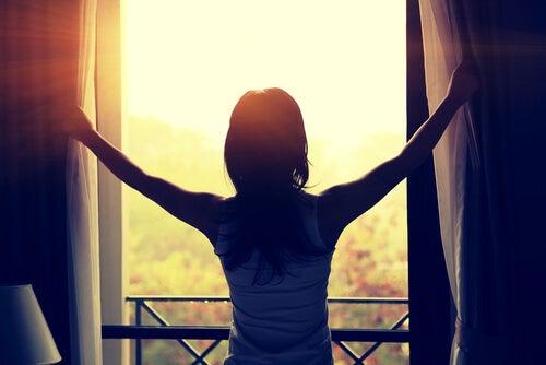 Mujer mirando el sol por la ventana