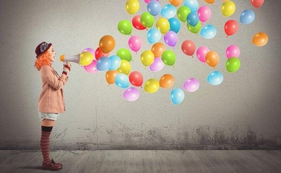 mujer payaso con megáfono del que salen globos haciendo el ridículo