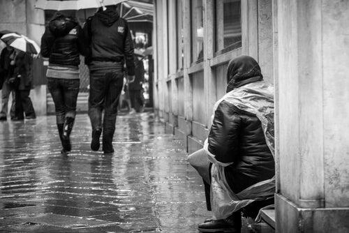 Mujer pidiendo en la calle para representar el efecto espectador