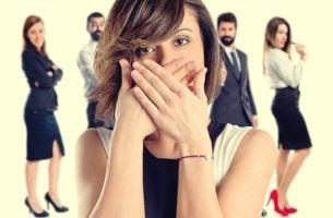 mujer que se tapa la boca porque tiene miedo a hablar en público