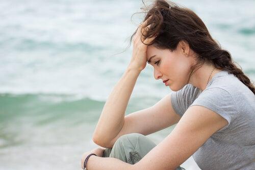 Mujer sentada frente al mar pensando que la vida es difícil