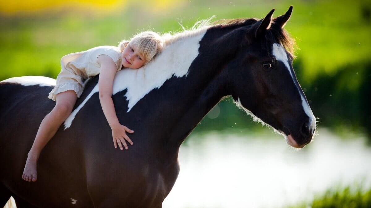 Niña abrazada a caballo