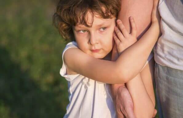 Niña agarrada al brazo de su padre