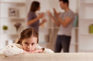 Niña escuchando cómo discuten sus padres sobre su castigo
