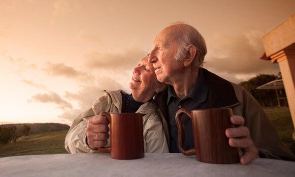 pareja mayor tomando algo al atardecer felices por envejecer saludablemente