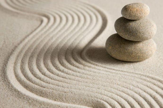 rocas sobre arena representando el coaching zen