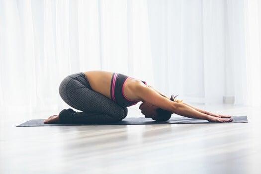 mujer haciendo yoga simbolizando las cosas que debes hacer antes de las 9 de la mañana