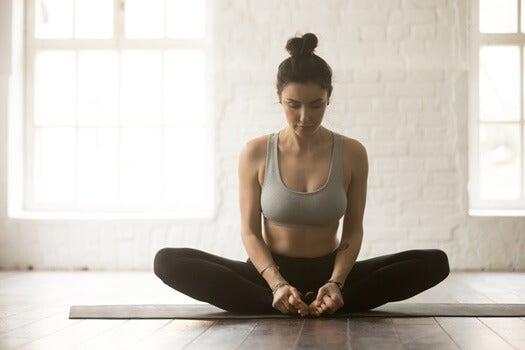 chica practicando yoga en casa representando el tratamiento según la teoría inflamatoria de la depresión