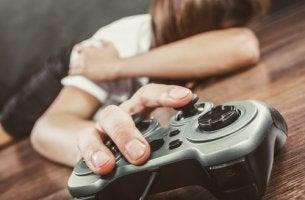 Adolescente en el suelo con un mando de la videoconsola para representar el trastorno de juego por internet