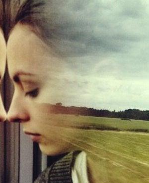 chica ante un cristal pensando en cómo deshacernos de las preocupaciones
