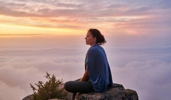 chica sentada en el silencio de una montaña simbolizando la dificultad del amor en las personas inteligentes