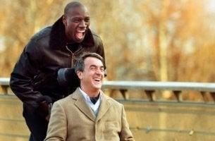 Chico llevando a un hombre en silla de ruedas portada de Intocable