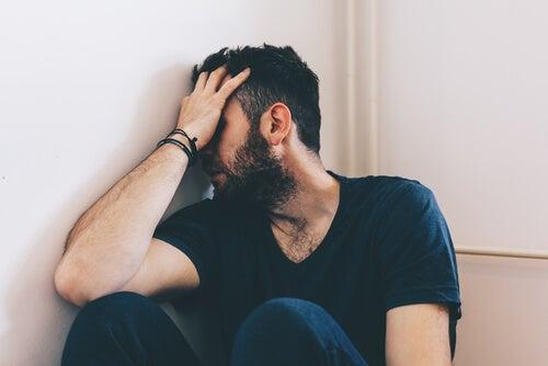 Hombre apoyado en la pared con la mano en la cara que sufre maltrato de pareja