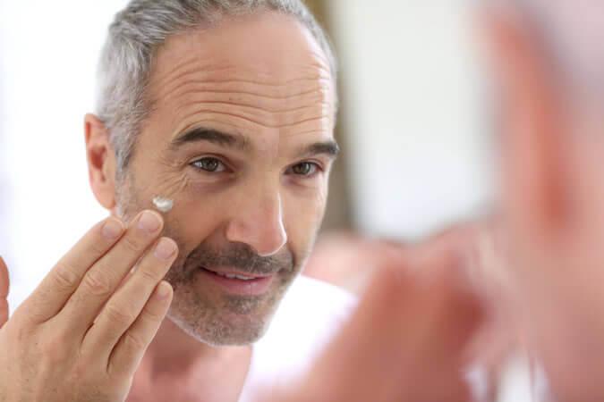 Hombre de 50 echándose crema
