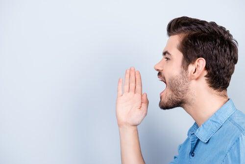 Hombre gritando con la mano cerca de la boca por el síndrome de Tourette