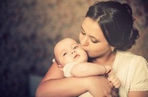 Madre dando un beso a su bebé