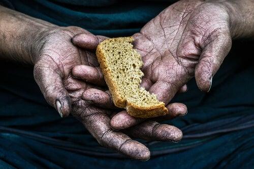 Mano con un trozo de pan de una persona pobre
