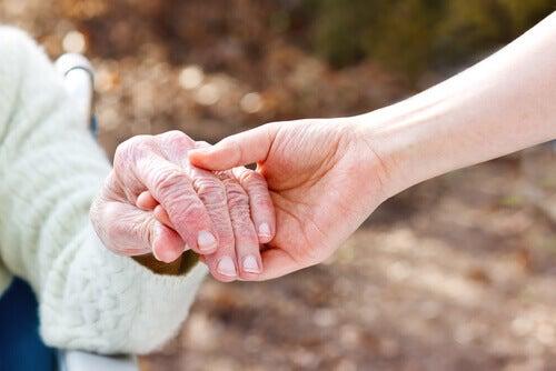 Mano de una persona joven sujetando la mano de una persona mayor