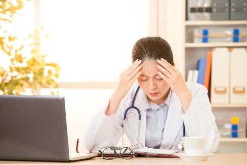 Médica cansada con las manos en la cabeza