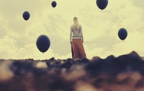 chica envuelta en globos oscuros representando la desesperanza creativa