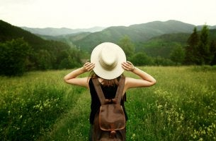 Mujer con sombrero en la montaña para representar a los viajeros incansables