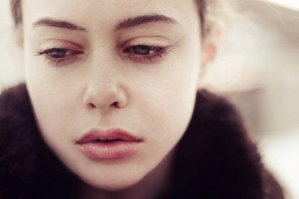 Mujer mirando hacia abajo con cara de tristeza por un recuerdo traumático