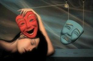 mujer sosteniendo máscaras que representan la Neurosis
