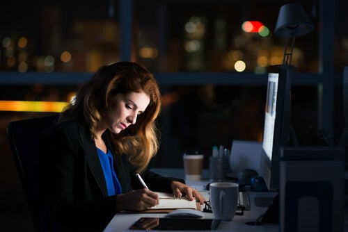 Mujer trabajando por la noche en la oficina para representar al workaholic