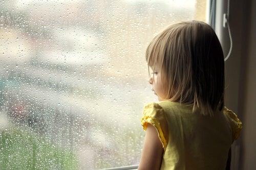 Niña mirando por la ventana que sufre heridas emocionales del pasado