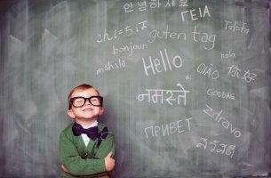 Niño con gafas delante de una pizarra con varios idiomas para representar el bilingïsmo