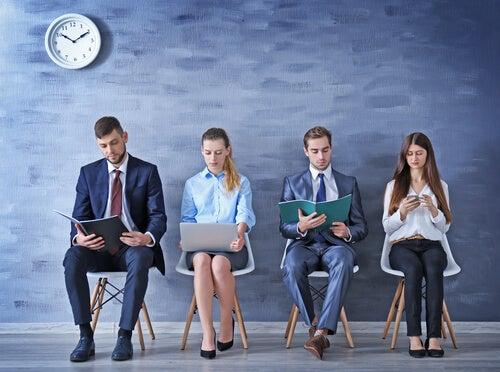 Personas sentadas esperando para hacer una entrevista de trabajo